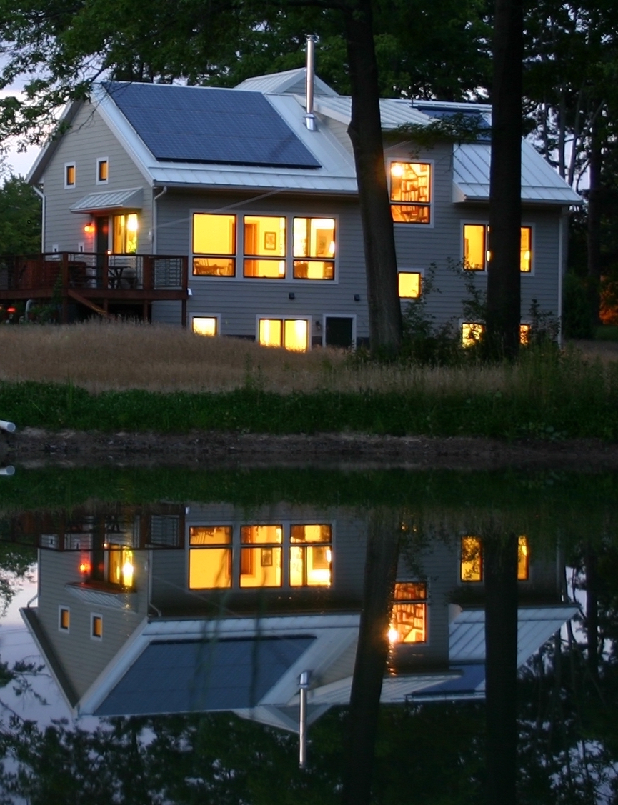 Trial Magic S and W sides reflected in pond at night; a positive energy home in Oberlin OH (photo Joe Ferut Ferut Architects)