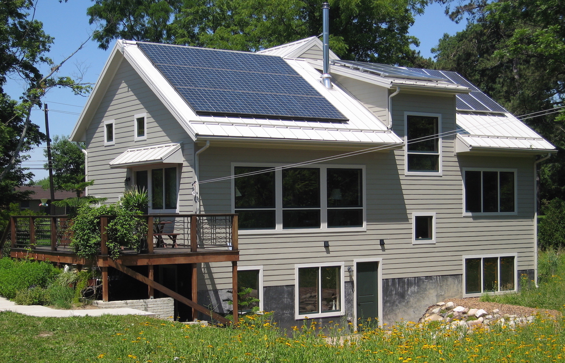 Trail Magic S and W sides showing PV panels deck and sun patio; a positive energy home in Oberlin OH