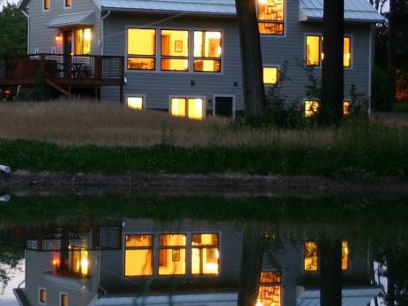 Trial Magic, S and W sides reflected in pond at night; a positive energy home in Oberlin, OH (photo, Joe Ferut, Ferut Architects)