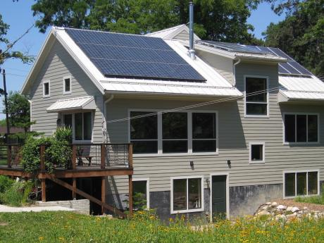 Trail Magic, S and W sides showing PV panels, deck and sun patio; a positive energy home in Oberlin, OH