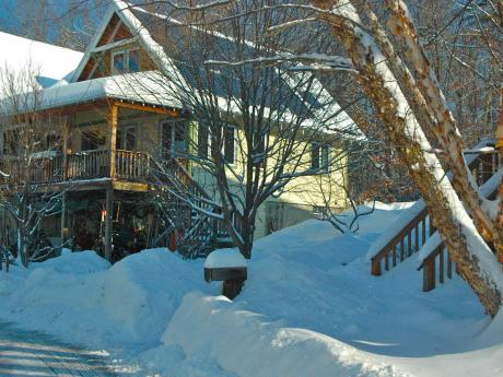 South view of renovated home after snow storm, showing PV collectors free of snow