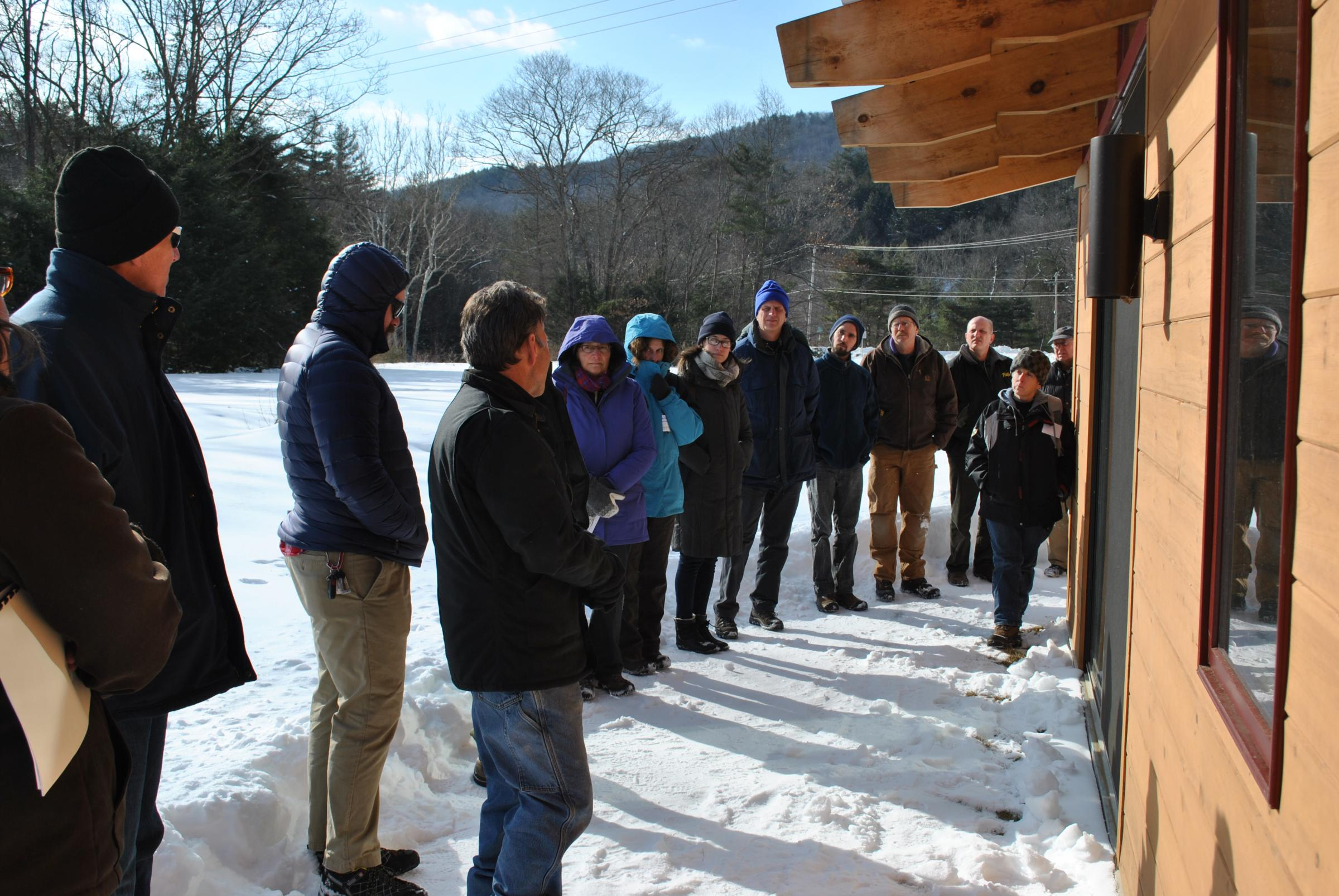 Group standing in a row next to a building during a BuildingEnergy Pro Tour (Caption: BuildingEnergy Pro Tour participants stand next to a building in Colrain, Mass. on Feb. 6, 2015.)